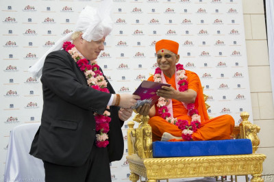 His Divine Holiness Acharya Swamishree presents the official glossy invitation to the grand opening of Shree Swaminarayan Mandir Kingsbury in August to the Mayor of London Boris Johnson