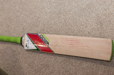 A close up of the signed bat
