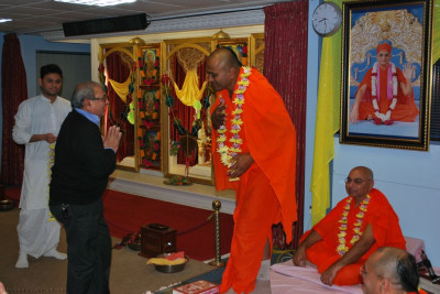 Disciples welcome Sant Shiromani Shree Dharmavatsaldasji Swami to London by offering a garland of fresh fragrant flowers