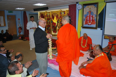 Disciples welcome Sant Shiromani Shree Sarvagunalaydasji Swami to London by offering a garland of fresh fragrant flowers