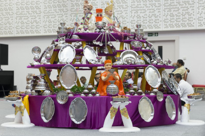 The splendid display of steel utensils arranged in a multi-tier ornament with Lord Shree Swaminarayanbapa Swamibapa giving His divine darshan at the centre