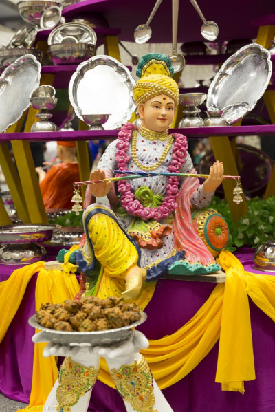 A close up of the splendid display of steel utensils arranged in a multi-tier ornament with Lord Shree Swaminarayanbapa Swamibapa giving His divine darshan at the centre