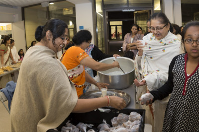 Disciples serve prasad of bhajia and doodh pawa (sweetened milk with flattened rice soaked in it) as is traditional for Sharad Poonam celebrations around the world