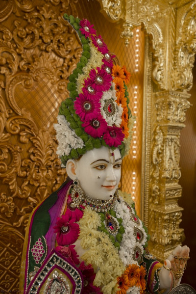 Divine darshan of Lord Shree Swaminarayan adorned in beautiful garments and a crown made from fresh bright flowers