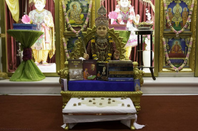 Divine darshan of Lord Shree Swaminarayan seated upon Shree Swaminarayan Gadi writing the Shikshapatri scripture