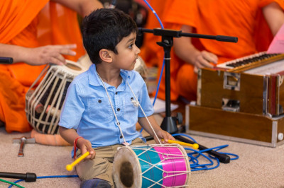 A young disciple plays a small version of a dhol
