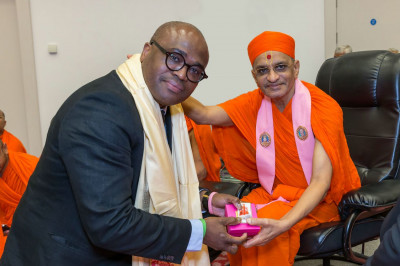 Councillor James Allie receives prasad and shawl from Acharya Swamishree