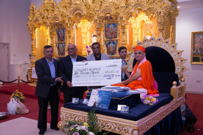 His Divine Holiness Acharya Swamishree together with the trustees of Shree Swaminarayan Mandir Kingsbury present a cheque for 10,000 raised by disciples through various charitable events to St. Luke's Hospice