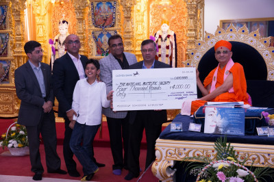 His Divine Holiness Acharya Swamishree together with the trustees of Shree Swaminarayan Mandir Kingsbury present a cheque for 4,000 raised by disciples through charitable events to the National Autistic Soceity