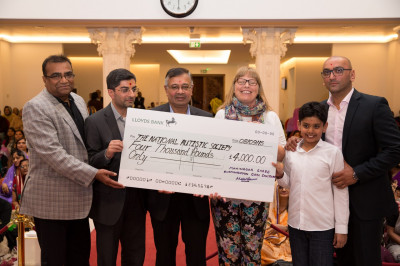 The trustees of Shree Swaminarayan Mandir Kingsbury present a cheque for 4,000 raised by disciples through charitable events to the National Autistic Soceity