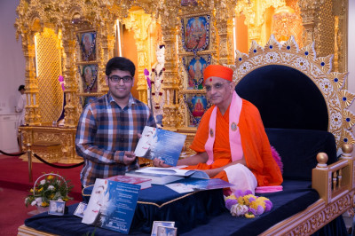 His Divine Holiness Acharya Swamishree presents an Excellence award to the disciple for very high educational attainment