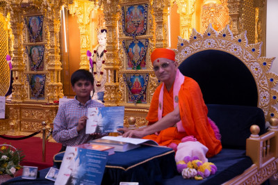 His Divine Holiness Acharya Swamishree presents a certificate of achievement to a young disciples for attaining high standards in Gujarati within Swamibapa Gujarati School