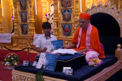 His Divine Holiness Acharya Swamishree presents a certificate of achievement to a young disciples for attaining high standards in the Sanskar Deepika 1 exam