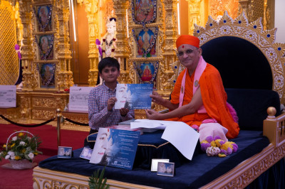 His Divine Holiness Acharya Swamishree presents a certificate of achievement to a young disciples for achiieving 100%  in the Sanskar Deepika 1 exam