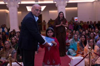 Honoured guests present certificates of achievement to young disciples for attaining high standards in Gujarati within Swamibapa Gujarati School