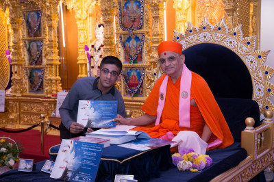 His Divine Holiness Acharya Swamishree presents a certificate of achievement to the young disciple