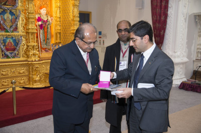 Shri Bhupendrasinh Jii Chudasama is presented with various publications and prasad by one of the trustees of Shree Swaminarayan Mandir Kingsbury