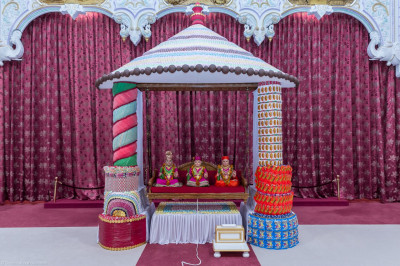 Divine darshan of Lord Shree Swaminarayan, Jeevanpran Shree Abji Bapashree and Jeevanpran Shree Muktajeevan Swamibapa seated on a hindola made from sweets and chocolates