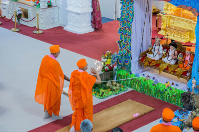 His Divine Holiness Acharya Swamishree performs aarti to Lord Shree Swaminarayanbapa Swamibapa seated in the peacock themed hindola