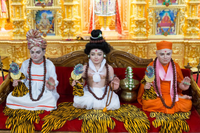 Divine darshan of Lord Shree Swaminarayan dressed as Nilkantvarni, Jeevanpran Shree Abji Bapashree and Jeevanpran Shree Muktajeevan Swamibapa seated on the hindola