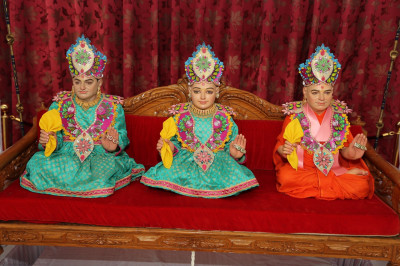 Divine darshan of Lord Shree Swaminarayan, Jeevanpran Shree Abji Bapashree and Jeevanpran Shree Muktajeevan Swamibapa seated on the hindola