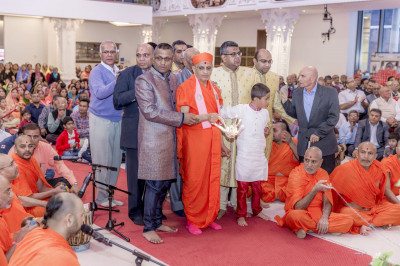 Acharya Swamishree performs aarti with disciples