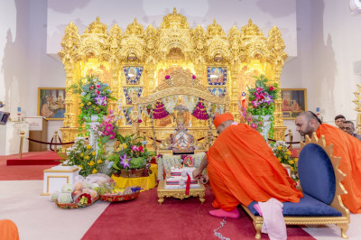 Acharya Swamishree cuts the cake and offers it to Lord Swaminarayan