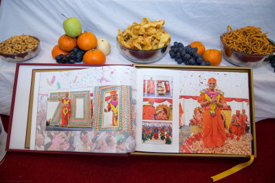 The red photo album capturing all of the events up to the grand opening of the mandir last year is presented to the Lord
