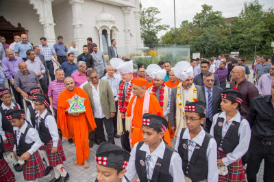Performers lead His Divine Holiness Acharya Swamishree towards the flags