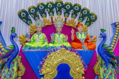 Divine darshan of Lord Shree Swaminarayan, Jeevanpran Shree Abji Bapashree and Jeevanpran Shree Muktajeevan Swamibapa seated on the grand stage