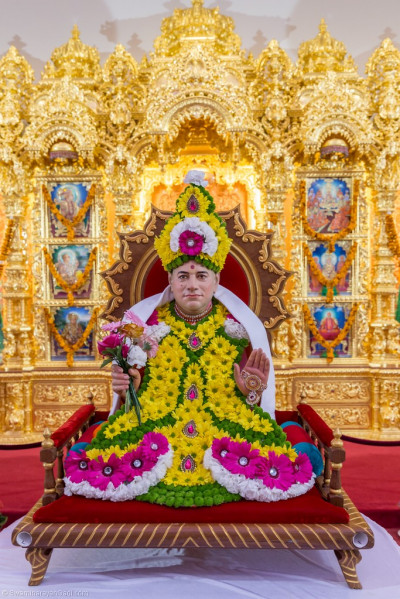 Divine darshan of Jeevanpran Shree Muktajeevan Swamibapa adorned in a crown and vagha made from brightly pink, green, yellow and white coloured fresh fragrant flowers