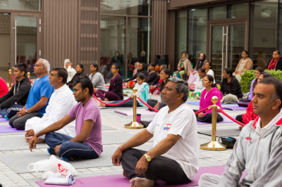 Disciples perform yoga celerating the first international world yoga day within the peaceful setting of Shree Muktajeevan Swamibapa Complex