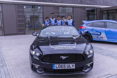 The Swamibapa FC team dressed in their new colours inside the Ford Mustang