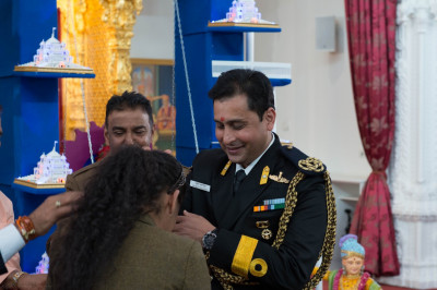 A disciple presents a rakhi to Commodore Sameer Saxena (Naval advisor to the Indian High Commission)