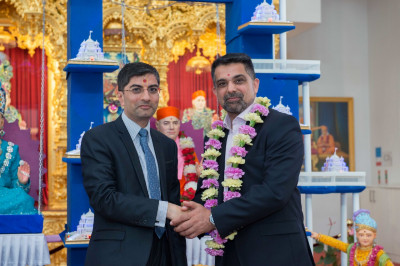 Dr. Mahesh Varsani - trustee of Shree Swaminarayan Mandir Kingsbury garlands Councillor Muhammed Butt