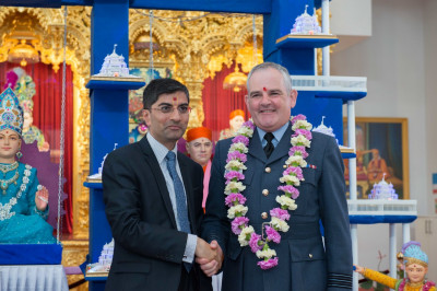 Dr. Mahesh Varsani - trustee of Shree Swaminarayan Mandir Kingsbury garlands Wing Commander Bob Bamford (SO1 BAME Recruitment and Selection, Royal Air Force)