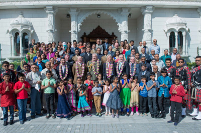 All honoured guests, disciples, and members of Shree Muktajeevan Swamibapa Pipe Band London outside the entrance of Shree Swaminarayan Mandir Kingsbury