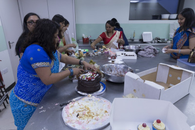 Disciples cut cake and prepare prasad