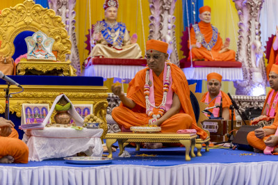 His Divine Holiness Acharya Swamishree showers fresh flower petals as the Lord's 108 divine names are recited