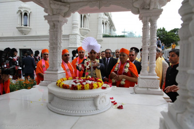 The Mayor places flower petals at the charnavind