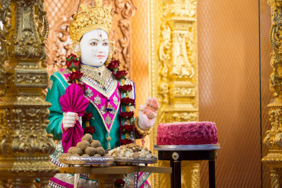 Divine darshan of Lord Shree Swaminarayan dining on the pink cake, popcorn and other Indian sweets