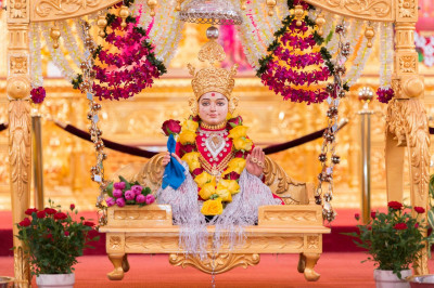 Divine darshan of Lord Shree Swaminarayan seated on a charming golden swing