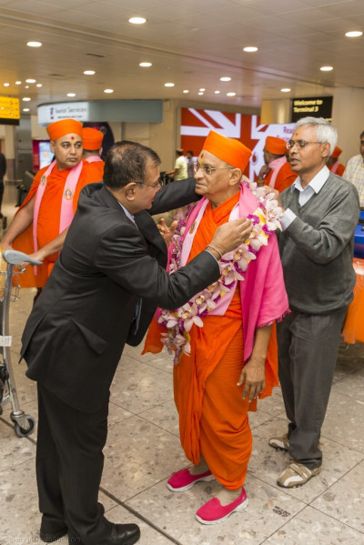 His Divine Holiness Acharya Swamishree is presented a garland of flowers
