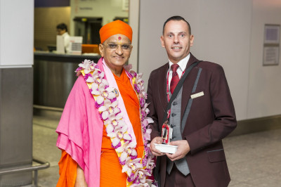 His Divine Holiness Acharya Swamishree blesses one of the passenger service agents