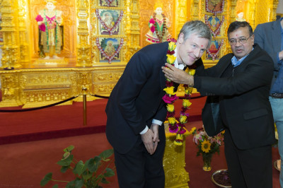 A garland of fresh flowers is presented to Zac Goldsmith