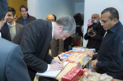 Zac Goldsmith signs the official Shree Swamianrayan Mandir Kingsbury visitor's book
