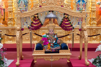 Divine darshan of Lord Shree Swaminarayan seated on the charming golden swing