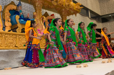 Young disciples perform a devotional dance on stage to please Lord Shree Swaminarayan