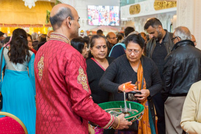 Visitors learn how to accept the darshan of the aarti flame