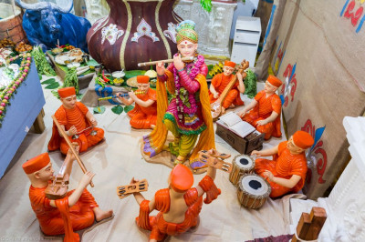 Divine darshan of Lord Shree Swaminarayan surrounded by sants performing various instruments
